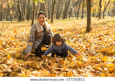 Happy mom and son playing in park with autumn leaves  - stock photo