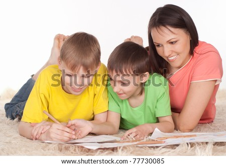 happy mom and sons drawing on the carpet - stock photo