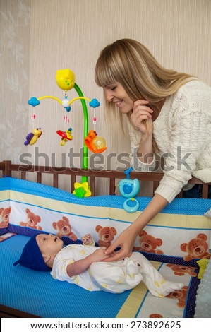 happy mom beside her baby cots - stock photo