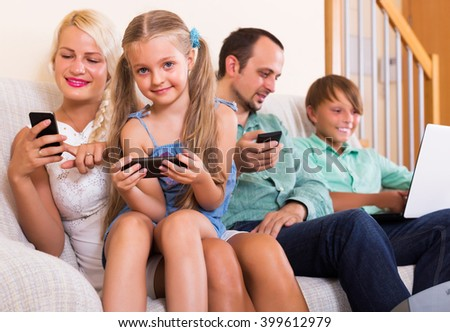 Happy mom, dad and two kids working with smartphones indoors