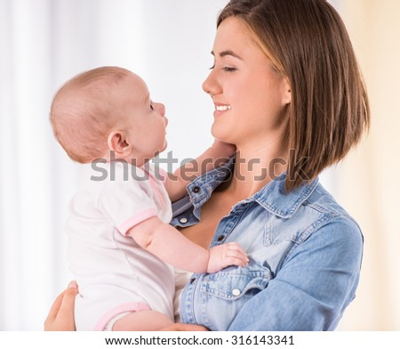 Happy mom is holding baby girl and looking at her. - stock photo