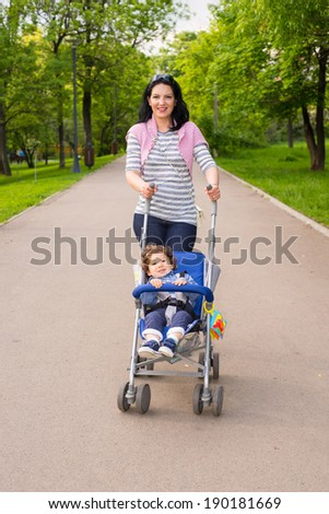 Happy mom pushing pram with toddler boy in park