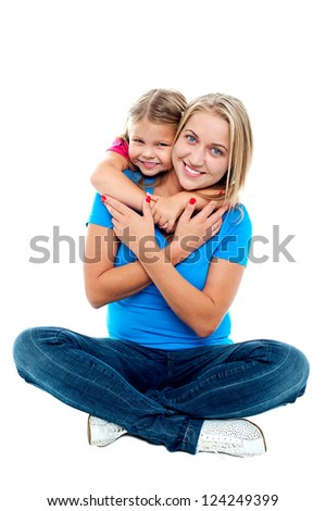Happy mom sitting on floor while daughter hugging her from behind. - stock photo