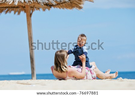 Happy mom with a child is resting at the sea