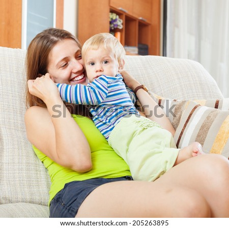 happy mom with child in home interior - stock photo