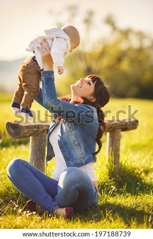 happy mom with child smiling playing at nature. Outdoor portrait - stock photo