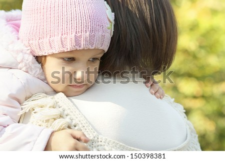 happy mom with her baby daughter for a walk in the autumn