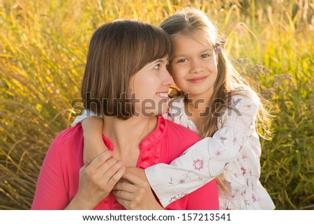 Happy mom with her school-aged daughter in an autumn park at dusk, with strong backlight - stock photo