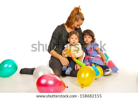 Happy mom with two kids sitting on floor with balloons - stock photo