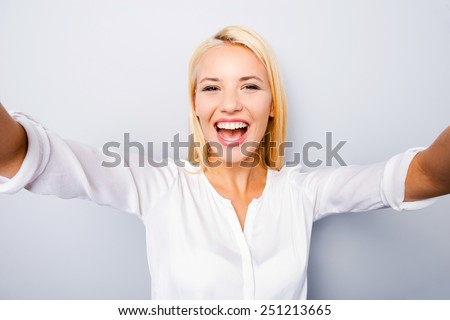 Happy moments must be saved. Cheerful young blond hair woman holding camera and making photo of herself while standing against grey background - stock photo
