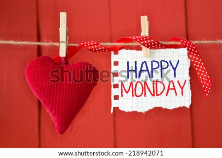 Happy Monday on instant paper and small red heart hanging on the clothesline. On red wood background - stock photo