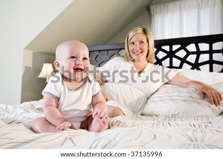 Happy 7 month old baby sitting on bed with mother - stock photo