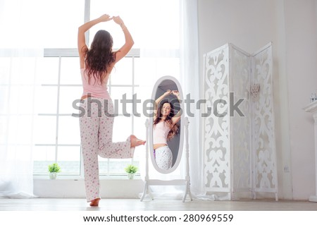 Happy morning. Attractive young woman dancing near mirror at her apartment. - stock photo