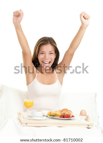 Happy morning breakfast woman smiling eating breakfast in bed stretching looking at camera. Beautiful morning fresh multicultural Asian Caucasian female model isolated on white background. - stock photo