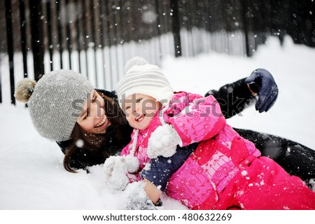 Happy Mother and adorable baby girl in cozy winter outfits on a winter walk in snowfall.