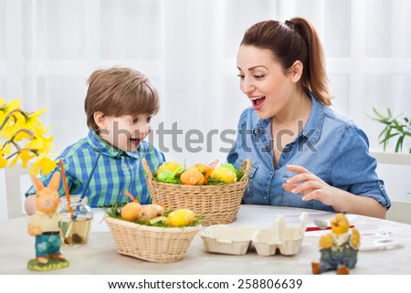 Happy mother and adorable child looking at easter colored eggs and smiling - stock photo