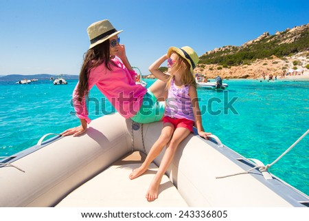 Happy mother and adorable girl enjoy vacation on boat - stock photo