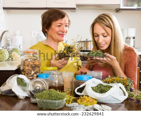 Happy mother and adult daughter sitting at the table with herbal tea and herbs  - stock photo