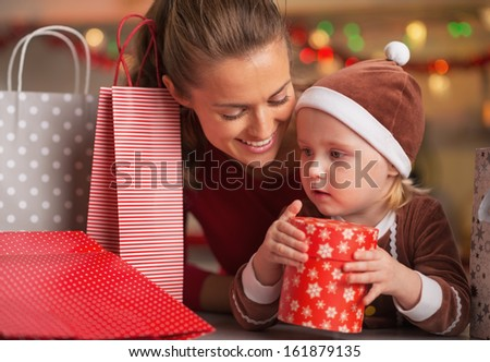 Happy mother and baby among christmas shopping bags - stock photo
