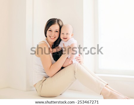 Happy mother and baby at home in light room - stock photo