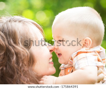Happy mother and baby boy having fun outdoors in spring park against natural green background - stock photo