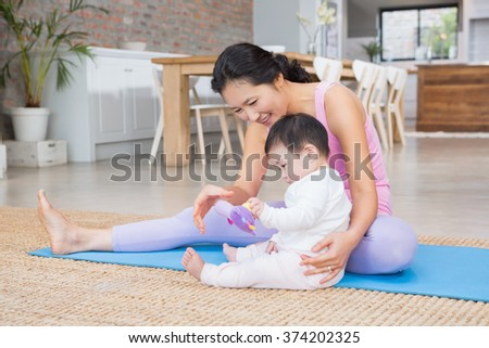 Happy mother and baby daughter sitting on exercising mat at home - stock photo