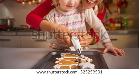 Happy mother and baby decorating homemade christmas cookies with glaze