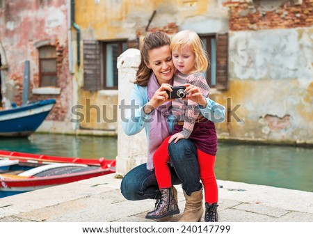 Happy mother and baby girl checking photos in camera while in venice, italy - stock photo