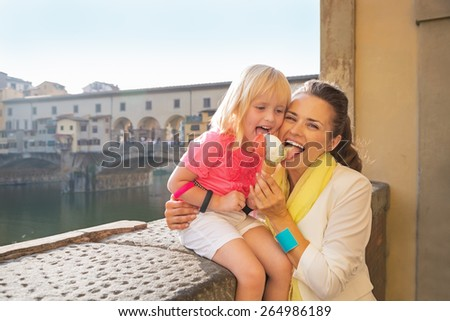 Happy mother and baby girl eating ice cream near ponte vecchio in florence, italy - stock photo