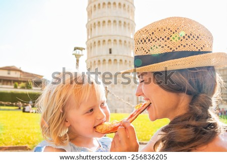 Happy mother and baby girl eating pizza in front of leaning tower of pisa, tuscany, italy - stock photo