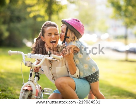 Happy mother and baby girl having fun in park with bicycle - stock photo