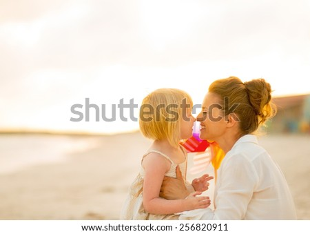 Happy mother and baby girl on beach at the evening - stock photo