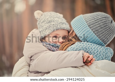 happy mother and baby girl on the walk in winter snowy forest - stock photo
