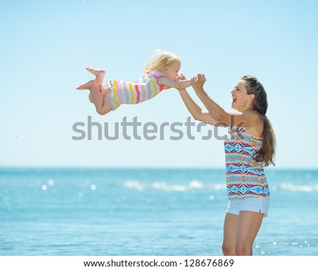 Happy mother and baby girl playing at seaside - stock photo