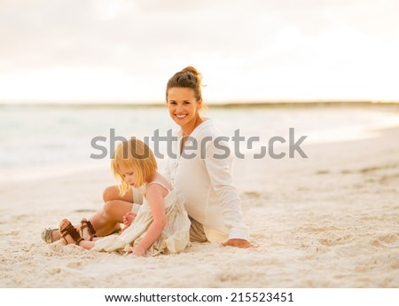 Happy mother and baby girl sitting on the beach in the evening - stock photo