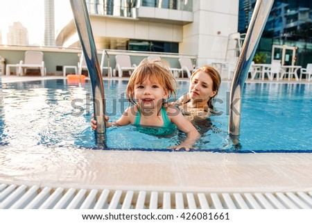 Happy mother and baby girl swimming and having fun in the swimming pool outdoors