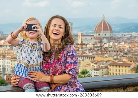 Happy mother and baby girl taking photo against panoramic view of florence, italy - stock photo