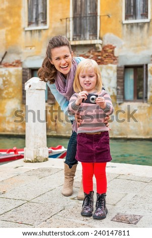 Happy mother and baby girl taking photo in venice, italy - stock photo
