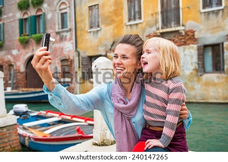 Happy mother and baby girl taking photo while in venice, italy - stock photo