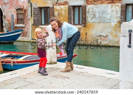 Happy mother and baby girl waving while walking in venice, italy - stock photo
