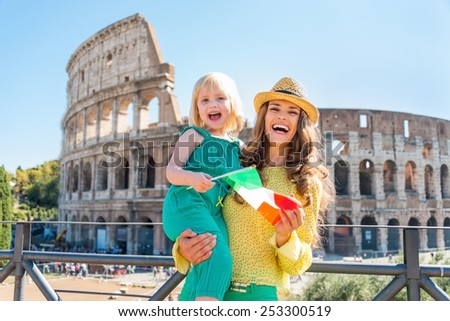 Happy mother and baby girl with italian flag in front of colosseum in rome, italy - stock photo