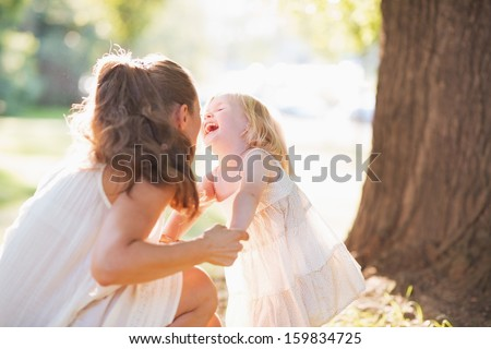 Happy mother and baby having fun in park - stock photo