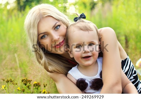 Happy mother and baby on nature background - stock photo