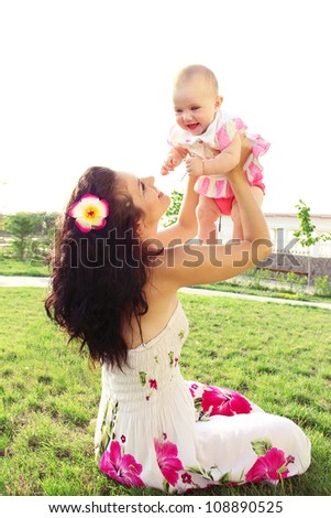 Happy mother and baby playing on field, outdoors - stock photo