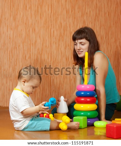 Happy mother and baby plays with pyramidion