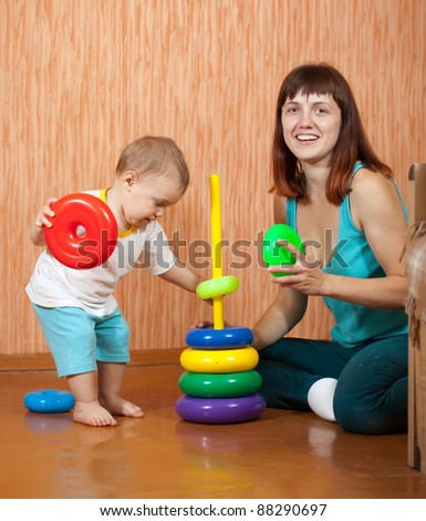 Happy mother and baby plays with pyramidion - stock photo