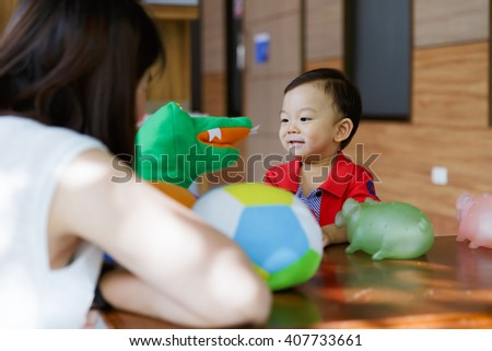 Happy mother and baby plays with toys at home - stock photo