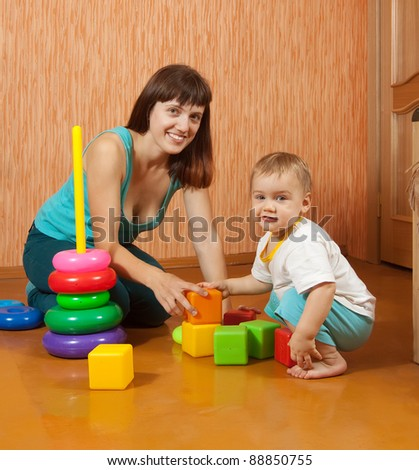 Happy mother and baby plays with toys at home interior - stock photo