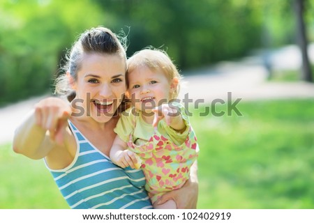 Happy mother and baby pointing in camera - stock photo