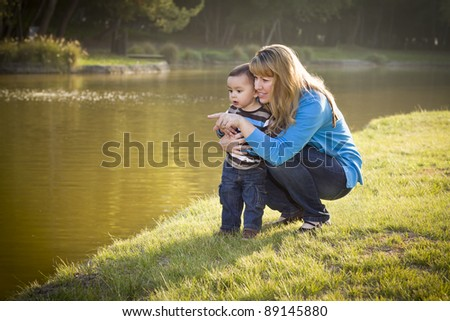 Happy Mother and Baby Son Looking Out At The Pretty Lake. - stock photo